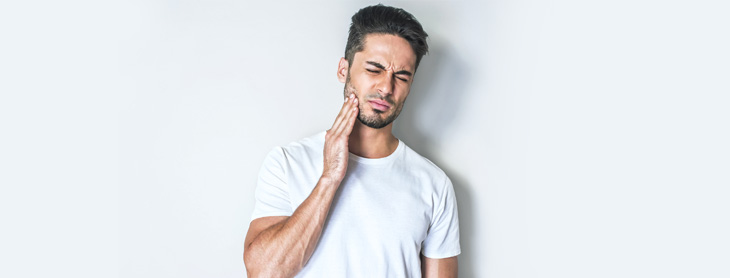 Man in pain holding his jaw