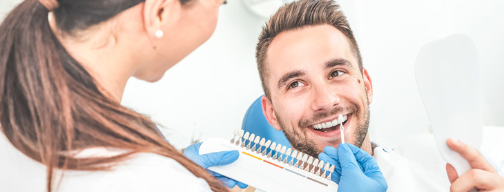 Dentist showing male patient options for implants